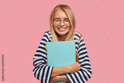 Fotografía  Happy overjoyed smiling teenager with blonde hair, keeps textbook closely, laugh