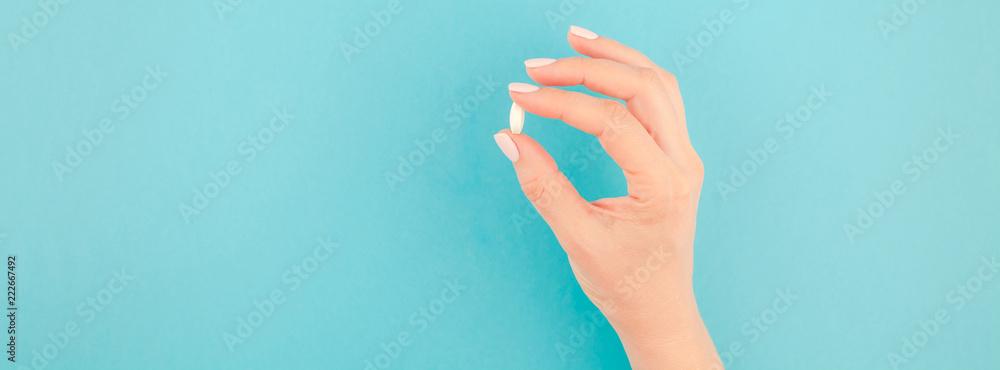 Fototapeta Female hand holding a white pill