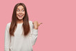 Photo of pleasant looking cute teenager has dark long hair, appealing look, dressed in casual white loose sweatshirt, points aside at blank copy space, stands over pink background. Look there