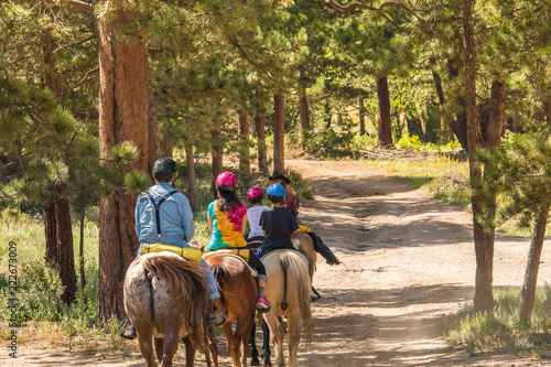 Fototapeta Family of four taking a horseback riding lesson in the woods in the Rocky Mountains, Colorado, in the summer obraz