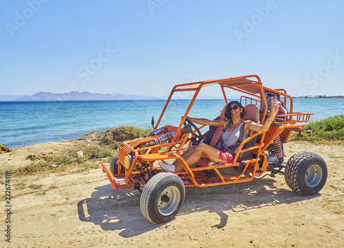 A happy girl driving a Buggy on a dune of beach with the Aegean sea in background Wallpaper Mural