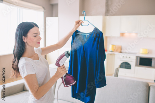 Fotografía Woman is steaming blue shirt in room