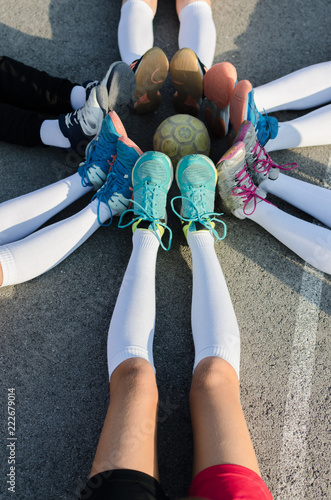 Legs of handball team players with ball in center