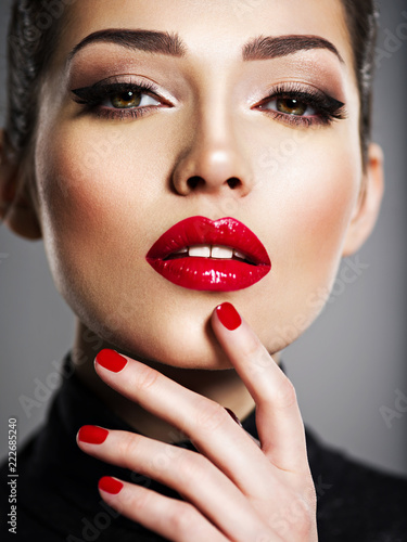 Obraz na plátně Beautiful woman with bright make-up and red nails.