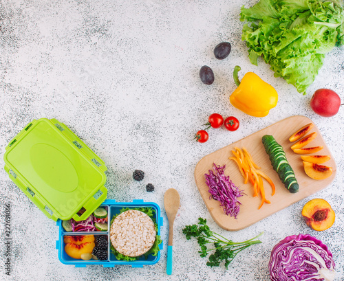 Foto op Aluminium Assortiment Blue lunch box with cover and ingredients on light background with copy space