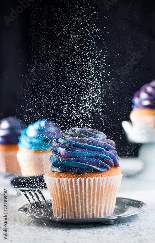Fotografia Vanilla cupcake sprinkled with sugar powder on black background