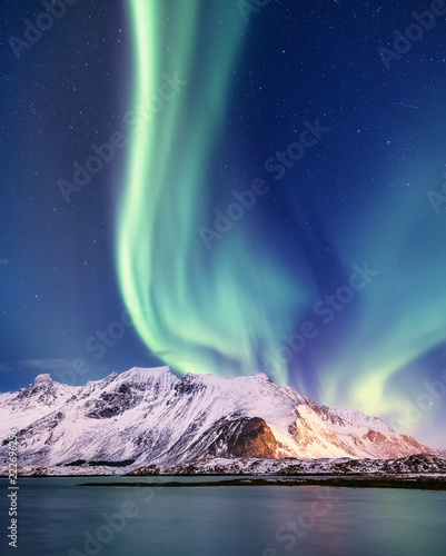 Poster Aurore polaire Aurora borealis on the Lofoten islands, Norway. Green northern lights above mountains. Night sky with polar lights. Night winter landscape with aurora and reflection on the water surface.