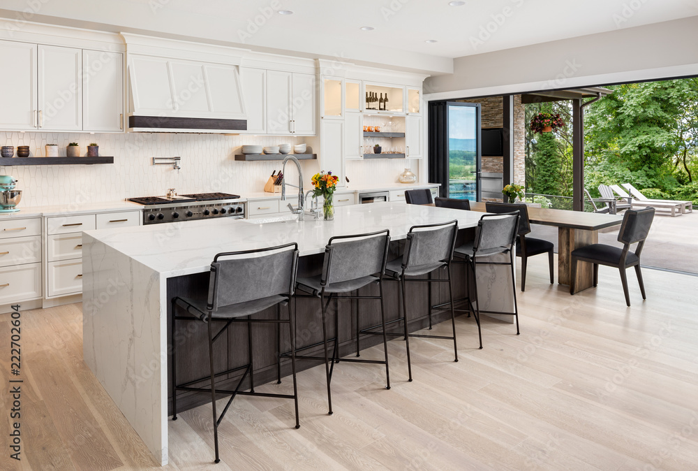 Fototapeta Kitchen interior in new luxury home with hardwood floors, waterfall island, dining room table, and accordion style glass doors. Glass doors are open showing exterior patio