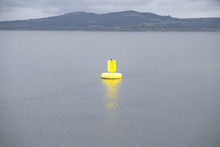 Yellow Buoy Bright Light In Open Sea Under Dark Grey Clouds And Mountain