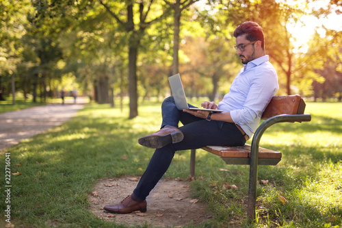 Foto  Handsome young businessman working on his laptop in the park