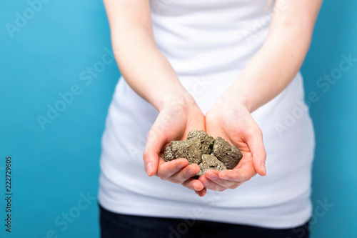 Young woman holding raw gold nuggets on a blue background - Buy this