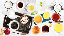 Set Of Different Cold Drinks And Hot Drinks - Juices, Coffee, Tea, Milk, Mint Water - Cups And Mugs Served On White Wooden Table. Closeup. Top View.