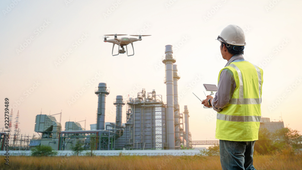 Fototapeta Drone inspection. Operator inspecting construction building  turbine power plant