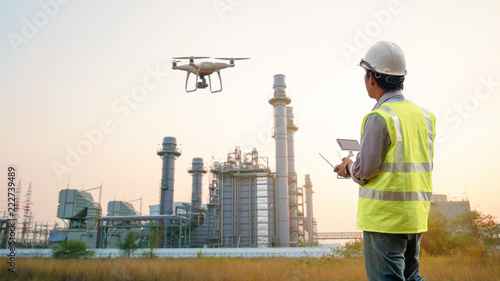 Fototapeta Drone inspection. Operator inspecting construction building  turbine power plant obraz