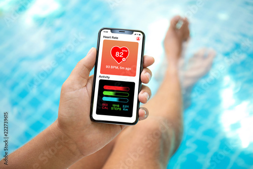 Fotografia  man at pool holding phone with app heart and activity