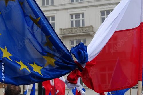 Fototapeta Flaga Unii Europejskiej i Polski splecione, związane razem, podczas demonstracji poparcia dla członkostwa Polski we Wspólnocie, w tle, rozmyte, budynki, inne flagi, głowa mężczyzny, z tyłu obraz