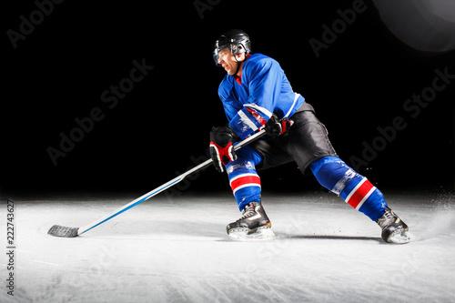 Photo Hockey player with stick turning around skating on ice against black background