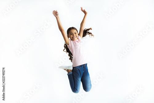 Fotografia The happy girl jumping on the white wall background