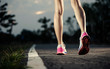 Runner feet running on running road closeup on shoe. woman fitness sunrise jog concept...