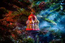 Red Shiny Decoration Christmas Balls Kremlin With House In Colored Purple-red Smoke, On An  Christmas Tree Background. Concept Of A Modern Christmas Card.