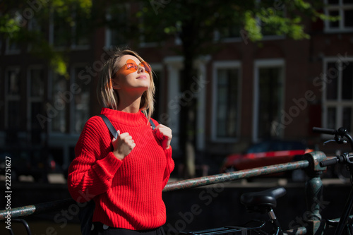 Photo  Young girl in red sweater and orange sunglasses with backpack at bridge in Amsterdam street
