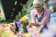 Senior Woman Sales Flowers On Local Flower Market