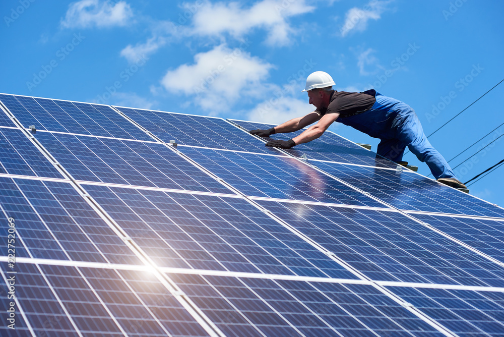 Fototapety, obrazy: Professional worker installing solar panels on the green metal construction, using different equipment, wearing helmet. Innovative solution for energy solving. Use renewable resources. Green energy.
