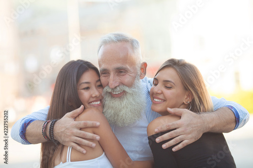 Fényképezés Happy Bearded senior man hugging his young friends.