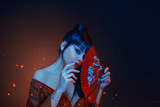 a beautiful geisha with blue long hair and a bang is looking in soul. red make up, lips, long dress with open shoders and deep neckline. holding scarlet fan in hands. Japanese east style, art photo