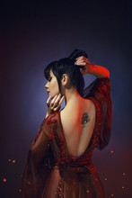 Young Girl With Dark Blue Hair And A Bang In A Long Red Dress With Open Naked Bare Back. A Tatoo Picture Lotus With A Shiny Piercing. Hands Near The Face And Hairdo. Gloomy Background With Highlights.
