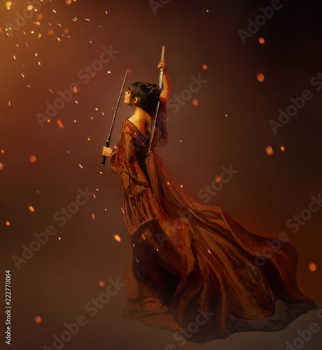 Fotografie, Obraz  young kunoichi girl samurai in a long dress with a lotus tattoo on the back, holding katana in hands