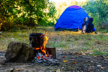 Cooking Food In A Kettle On Bonfire. Tent On Background