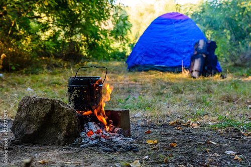 Cooking food in a kettle on bonfire. Tent on background Canvas Print