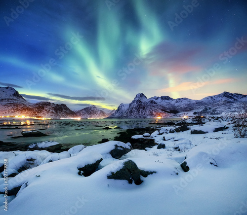 Photo sur Toile Aurore polaire Aurora borealis on the Lofoten islands, Norway. Green northern lights above mountains. Night sky with polar lights. Night winter landscape with aurora and reflection on the water surface.