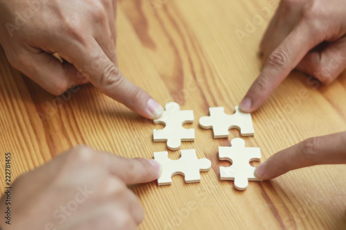 Fototapety, obrazy: Four Business People hands trying to connect couple puzzle piece .one part of whole. symbol of association and connection. business strategy.Partnership SALES Team Collaborate with Competitors.