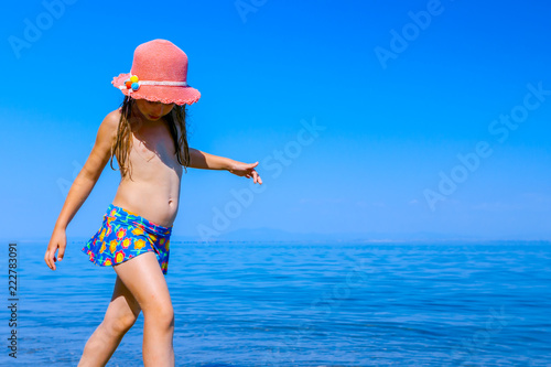 Valokuvatapetti Child girl in summer straw hat is dancing happy barefoot in shallow sea water, b