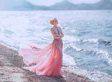Lovely Slender Girl In A Light Pink Dress Is Walking Along The Sandy Shore Of The Beautiful Blue Sea. Glare Of The Sun Is Reflected In The Waves. Wonderful Elegant Princess Elf With Blond Wavy Hair