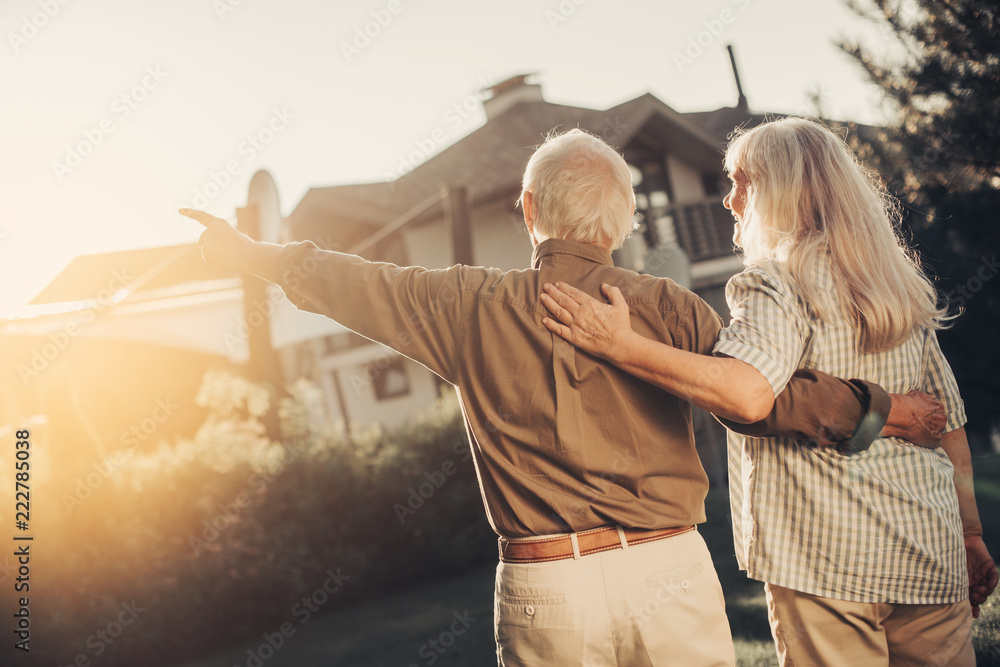 Fototapety, obrazy: Bright future. Cheerful twosome embracing and looking up man pointing at. They standing back to camera on lawn fronting house. copy space on left side