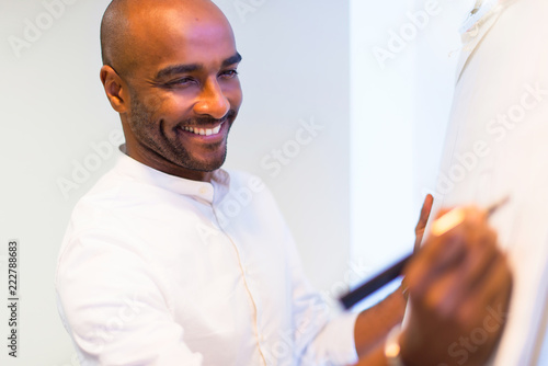 Fotografía  Young afro american businessman in the office writing on whiteboard a planning s