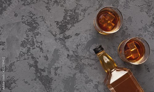 Photo Two glasses of whiskey and bottle aside on marble background
