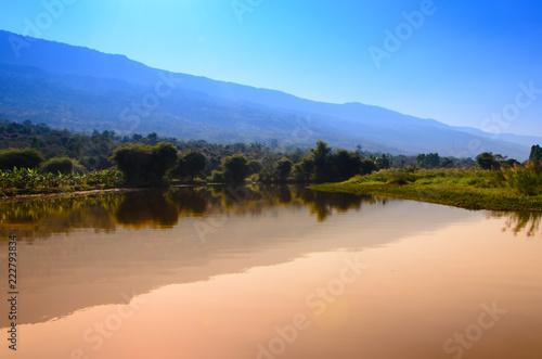 Montage in der Fensternische Honig Blue sky with mountain landscape view reflects on water