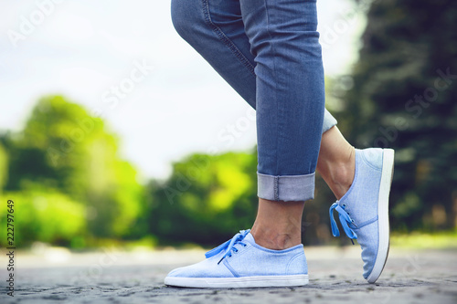 legs of a girl in jeans and blue sneakers on a sidewalk tile, a young woman stro Fototapeta