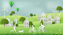 Paper Folding Art Origami Style Vector Illustration. Green Sustainable Energy Ecology Development Concept Father & Son Riding Bicycle, Mother & Dog Jogging In Village Parks Which Full Of Wind Turbine.