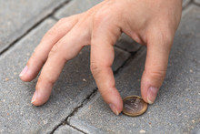 Female Hand Picking One Euro Coin From The Ground