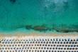 Aufgereihte Sonnenschirme und Sonnenliegen am Strand von Kalafatis auf Mykonos, Griechenland