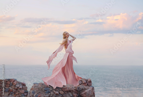 Foto elegant girl elf with blond fair wavy hair with tiara on it, wearing a long light pink rose rozy fluttering dress, standing on the high tower of the old castle