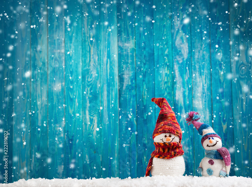 Obraz little knitted snowmans on soft snow on blue background - fototapety do salonu