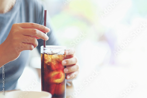 closeup woman Hand holding glass of cola drink in restaurant background, Woman hand glass soft drinks with ice