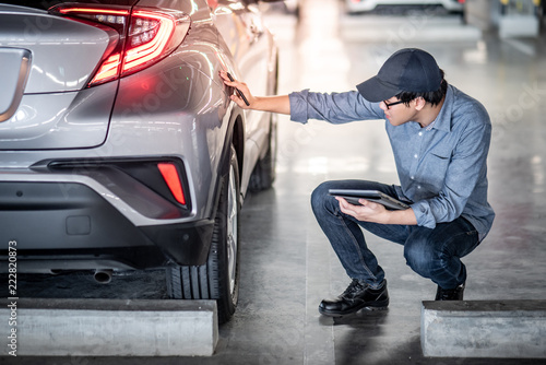 fototapeta na ścianę Young Asian auto mechanic holding digital tablet checking car wheel in auto service garage. Mechanical maintenance engineer working in automotive industry. Automobile servicing and repair concept