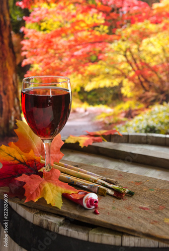 фотография  Glass of red wine, grapes and paint brushes on a wine barrel